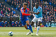 Crystal Palace midfielder Andros Townsend (10) battles for possession with Manchester City defender Benjamin Mendy (22) during the Premier League match between Crystal Palace and Manchester City at Selhurst Park, London, England on 14 April 2019.