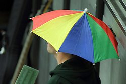 A pep band member elevates the craziness of a basketball game by wearing a brightly colored umbrella hat to help lighten the spirits in the arena