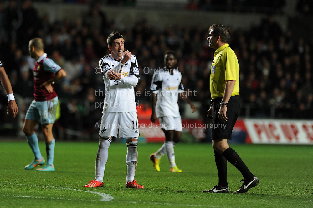 Swansea's Pablo Hernandez has words with referee Phil Dowd after a late injury time shot by Swansea city's Nathan Dyer appeared to hit the arm of West Ham's Joe Cole (c)in the penalty area. Barclays Premier League, Swansea city v West Ham Utd at the Liberty Stadium in Swansea,  South Wales on Sunday 27th Oct 2013. pic by Andrew Orchard, Andrew Orchard sports photography,