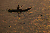 Lake Atitlan, Guatemala.  The sunset is reflected on the water as a Guatemalan fisherman paddles his wooden boat across the lake.