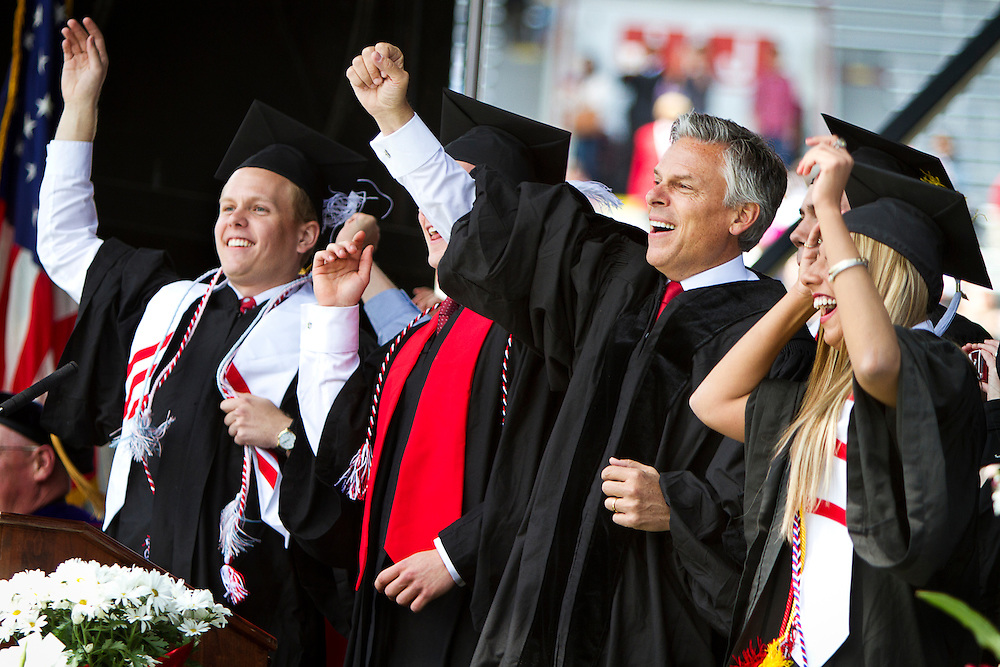 """Governor Jon Huntsman, Jr., center-right, does the """"Jump Around"""" on stage during the University of Wisconsin-Madison commencement ceremony at Camp Randall Stadium, Saturday, May 17, 2014."""