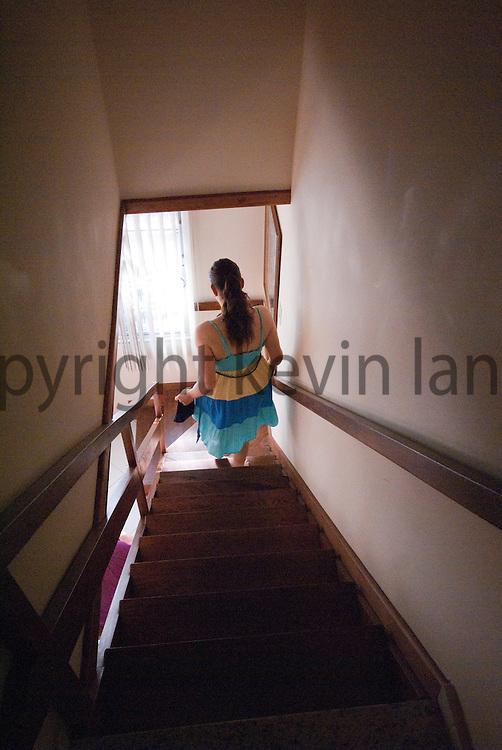 woman descending stairs at an apartment in cabo frio, rio de janeiro, brazil.