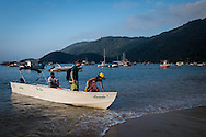 A water taxi offloads passengers stright onto the beach at Abraao on the island of Ilha Grande, Brazil. Photo by Andrew Tobin/Tobinators Ltd