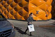 A shopper passes-by the temporary renovation hoarding of luxury brand Louis Vuitton in New Bond Street, on 25th February 2019, in London, England.