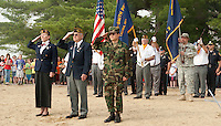 Doris Brady American Legion Post 1 Commander, Don Doherty Commander of Laconia Veterans of Foreign Wars Post 1670 and Greg Schneberger former Marine and guidance councilor at MMS stand at attention during the gun salute as Laconia Middle School students celebrate Memorial Day Services at Opechee Cove Friday morning.  (Karen Bobotas/for the Laconia Daily Sun)