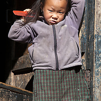 A girl combing her hair as we pass her house, somewhere between Phakding and <br /> Monjo.