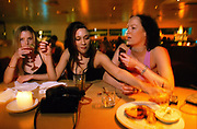 Three girls eating and drinking at Ion Bar Ladbroke Grove London April 2000