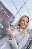 Happy businesswoman looking away while holding digital tablet against office building