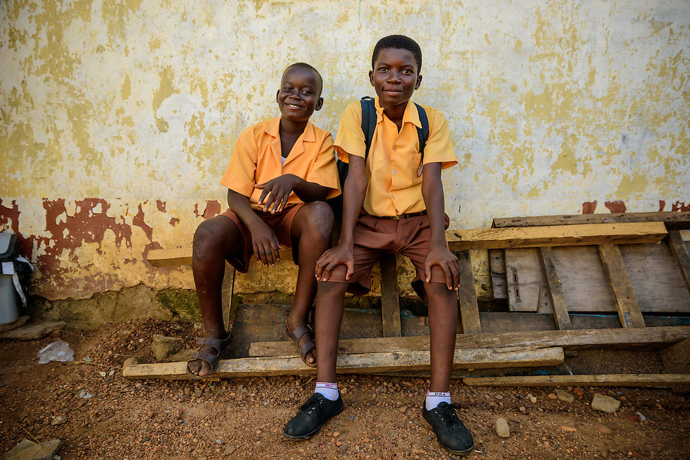 Two schoolboys are sitting on a bench and laugh in one of East Africa's biggest slums, Ghana.
