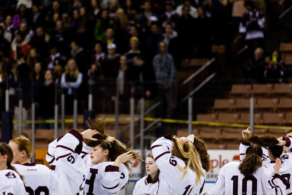 Hanover players tie their hair after removing their helmets for the post-game award ceremony after beating Berlin-Gorham for the NHIAA Division I girls hockey championship at Verizon Wireless Arena in Manchester, N.H., on March 15, 2014. Hanover won, 5-1. (Valley News - Will Parson)