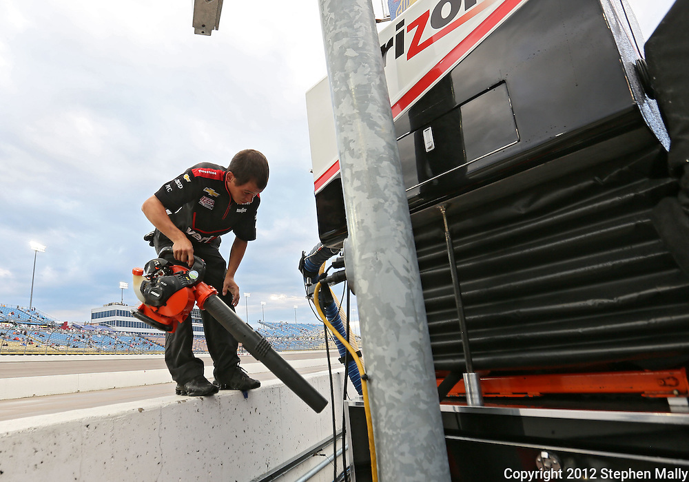 A worker blows off water from the equipment in the pit of WillPower before the start of the IZOD IndyCar Iowa Corn Indy 250 auto race at the Iowa Speedway in Newton, Iowa on Saturday, June 23, 2012.