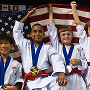 Ten year old national champions raise the American flag at USA Karate National Championships in Greenville, SC on July 10, 2010.  © 2010 Shelley Lipton.