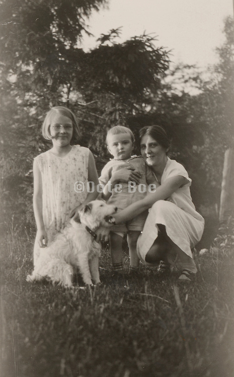 Group photograph of mother with her children and house pet