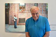 Huntington, New York, USA. August 1, 2015. GEORGE CARRANO poses by a photo of neighbors by Jane Mary Saiter, at the Reception for Project Lives exhibition at fotofoto gallery. Over 200 residents throughout 15 New York Public Housing projects were given single use film cameras to photograph what's important to them in their world. The photography project was originated by Carrano and the book Project Lives was edited by Carrano, C. Davis and J. Fisher, with all royalties from its sale to be donated to resident programs at NYC Housing Authority. The gallery is on the Gold Coast of Long Island.