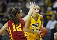 December 09 2010: Iowa guard Jaime Printy (24) looks to pass around Iowa St. guard/forward Jessica Schroll (12) during the first half of their NCAA basketball game at Carver-Hawkeye Arena in Iowa City, Iowa on December 9, 2010. Iowa defeated Iowa State 62-40 in the Hy-Vee Cy-Hawk Series rivalry game.
