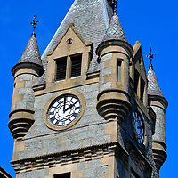 Clock Tower of Stewart's Hall in Huntly, Scotland <br /> This impressive clock tower with four turrets was constructed with Syllavethy granite based on the design of James Anderson.  It served as the Huntly town hall when it opened on Gordon Street in 1875. It was reconstructed in 1890 after a major fire three years before.  Stewart's Hall is now a venue for concerts and other entertainment events. This 338 seat theater often hosts performances in partnership with the Aberdeen Performing Arts.