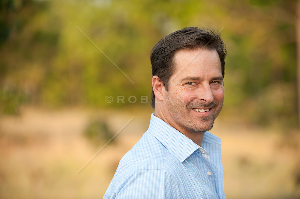 Man smiling wearing a button down blue shirt looking back over his shoulder