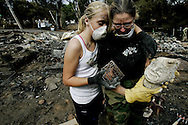 Kora Minor consoles neighbor Andrea Beckwith after she found a statue that Beckwith's Mother gave her her Mother in 1942, at her burned-out home in the Del Dios area of Escondido, California.  Firefirghters are gaining ground on several fire around Southern California as residents return to their homes.  As of Saturday, the Witch fire has burned approximately 197,990 acres and is at 60% containment.