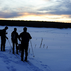 Friends enjoy the sunset before gliding across the open meadows on their   cross country skis in the Zuni Mountains of New Mexico.