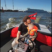 Nederland, Amsterdam, 29-05-2009 - Vader knuffelt zijn zoontje terwijl hij vaart in een vlet op Het Ij tijdens zijn papadag.   Foto: Gerard Til