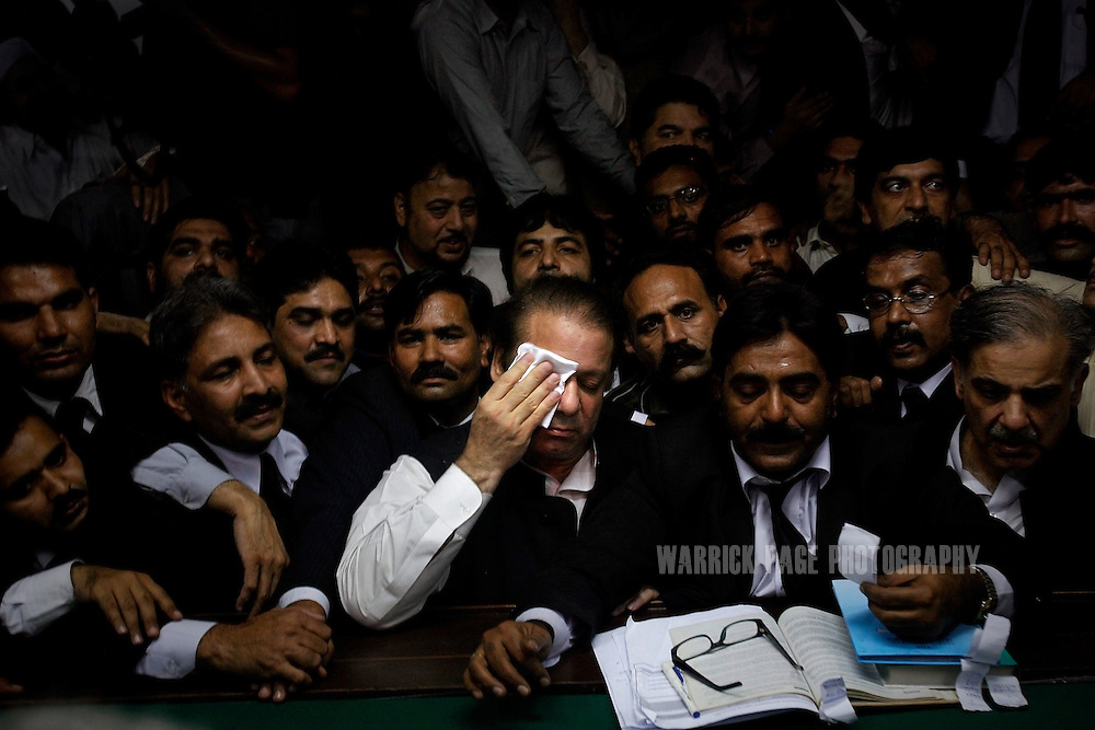 LAHORE, PAKISTAN - NOVEMBER 26: Former Prime Minister Nawaz Sharif wipes the sweat from his brow as his lawyers hand over his nomination papers for the upcoming general election at the Lahore electoral commission on November 26, 2007 in Lahore, Pakistan. Sharif, deposed and sent into exile eight years ago by President Pervez Musharraf, has hinted that he may boycott the elections if the state of emergency remains in place. (Photo by Warrick Page)