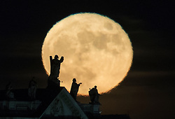 © Licensed to London News Pictures. 14/12/2016. London, UK. The last Super Moon of 2016 rises above some statues on the London skyline near Blackfriars Bridge. Photo credit: Peter Macdiarmid/LNP