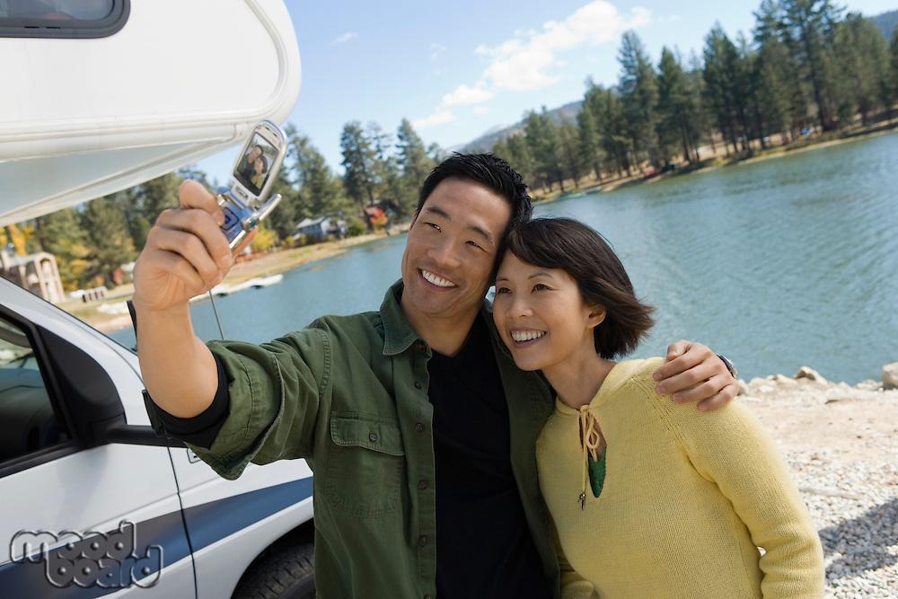 Couple Using Cell Phone Camera at Lake