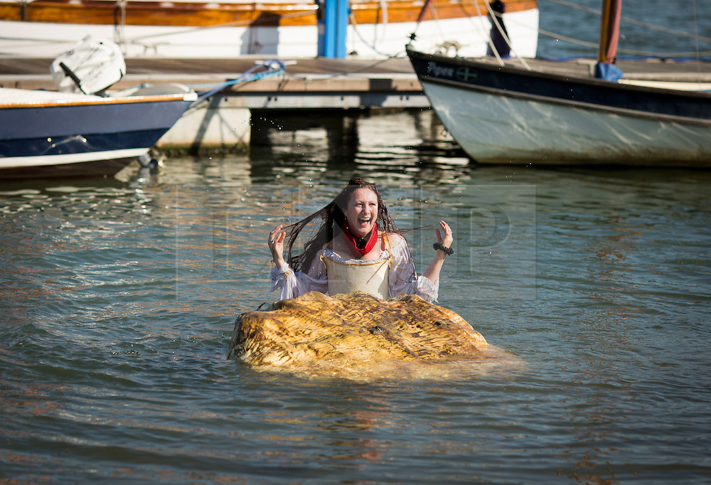 © Licensed to London News Pictures. 06/09/2015. Wells next the Sea , North Norfolk , UK.<br /> Sunny weather at The Wells next the sea Pirate Festival , Wells next the Sea , North Norfolk. <br /> The Black Knight Historical Society.<br /> Molly the Pirate falls off her Conacle into the water.<br /> Photo credit : Chris Bull/LNP