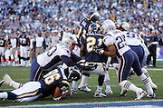 SAN DIEGO - JANUARY 14:  Running back LaDainian Tomlinson #21 of the San Diego Chargers scores a touchdown on a 2 yard run in the second quarter for a 7-3 lead over the Pats despite getting hit by Artrell Hawkins #25 and Richard Seymour #93 of the New England Patriots at the AFC Divisional Playoff Game held on January 14, 2007 at Qualcomm Stadium in San Diego, California. The Patriots defeated the Chargers 24-21. ©Paul Anthony Spinelli *** Local Caption *** LaDainian Tomlinson;Artrell Hawkins;Richard Seymour