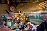 A Buddhist layman is relaxing under a reclining Buddha at Wat Nokor, a well known Buddhist temple in Kampong Cham, Cambodia.
