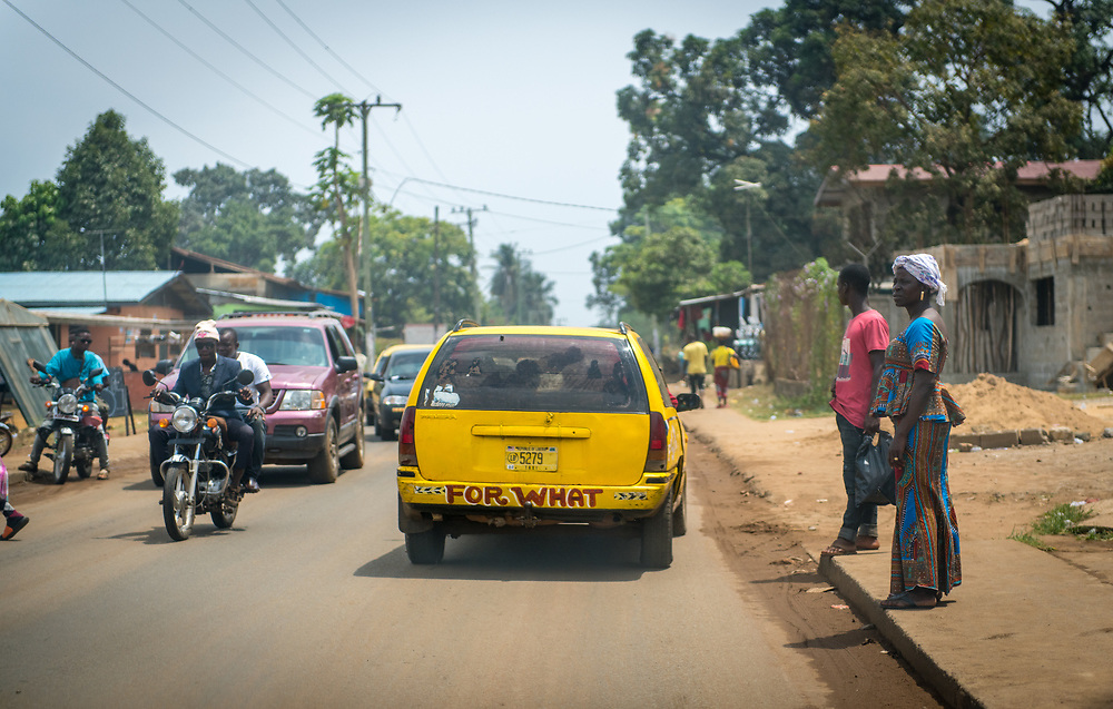 Motorists travel down a bustling street while people wait to cross in the city of Monrovia, Liberia