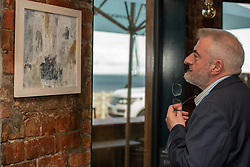 Art Walk Porty founder and producer Rosy Naylor shows local MP Tommy Sheppard around some of the work and meets some of the artists in this year's Art Walk in Portobello. Pictured:<br /> Tommy Sheppard in The Boathouse with work by Mary Walters. © Jon Davey/ EEm