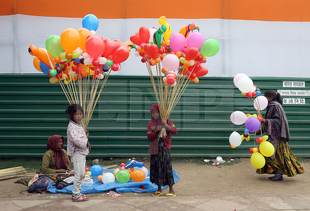 © Licenced to London News Pictures. 26//01/2015. Delhi. India.  <br /> Children sell balloons to revellers at India Gate on Republic Day in New Delhi, India, January 26th 2015. President Barack Obama was the chief guest in a show of solidarity between the world's two largest democracies in the face of an increasingly assertive China.<br /> Photo Credit: Susannah Ireland