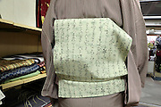 close up of a person wearing Japanese obi with ancient calligraphy back view