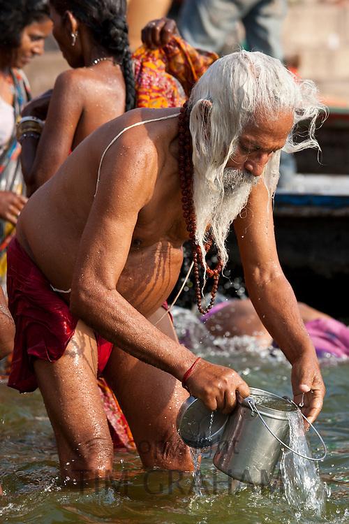 Indian Hindu pilgrim bathing in The Ganges River at Dashashwamedh Ghat in Holy City of Varanasi, Benares, India