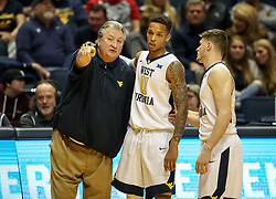 Dec 20, 2017; Morgantown, WV, USA; West Virginia Mountaineers head coach Bob Huggins talks with West Virginia Mountaineers forward D'Angelo Hunter (11) and West Virginia Mountaineers guard Chase Harler (14) during the second half against the Coppin State Eagles at WVU Coliseum. Mandatory Credit: Ben Queen-USA TODAY Sports