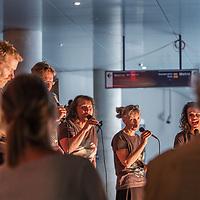 Nederland, Amsterdam, 2 juli 2017.<br />GENETIC CHOIR presenteert SOUNDWALKS  AMSTERDAM CS<br /> <br /> Geluidswandelingen (bovengronds): Geluidswandelingen op Amsterdam CS, waarbij u de geluiden van het station als symfonie leert ervaren. Na afloop kunt u zelf geluidssamples bijdragen voor het concert van 2 juli.<br />Het vocale improvisatie ensemble Genetic Choir maakt geluiden van het station als muziekstuk beluisterbaar. In het ondergrondse nieuwe metrostation Amsterdam CS van de Noord/Zuidlijn verklankt het koor, samen met laptopmusicus Robert van Heumen en met participatie van het publiek, gesampelde stationsgeluiden ter plekke tot een concert. De premi&egrave;re van Loop-Copy-Mutate vindt plaats in vier concerten op zondag 2 juli 2017. De locatie is het bordes van het metrostation Amsterdam CS van de Noord/Zuidlijn. Doel van de premi&egrave;re op 2 juli: Genetic Choir cre&euml;ert met het publiek een muziekstuk zo levend en veranderlijk als de stad zelf<br /><br /><br />Foto: Jean-Pierre Jans