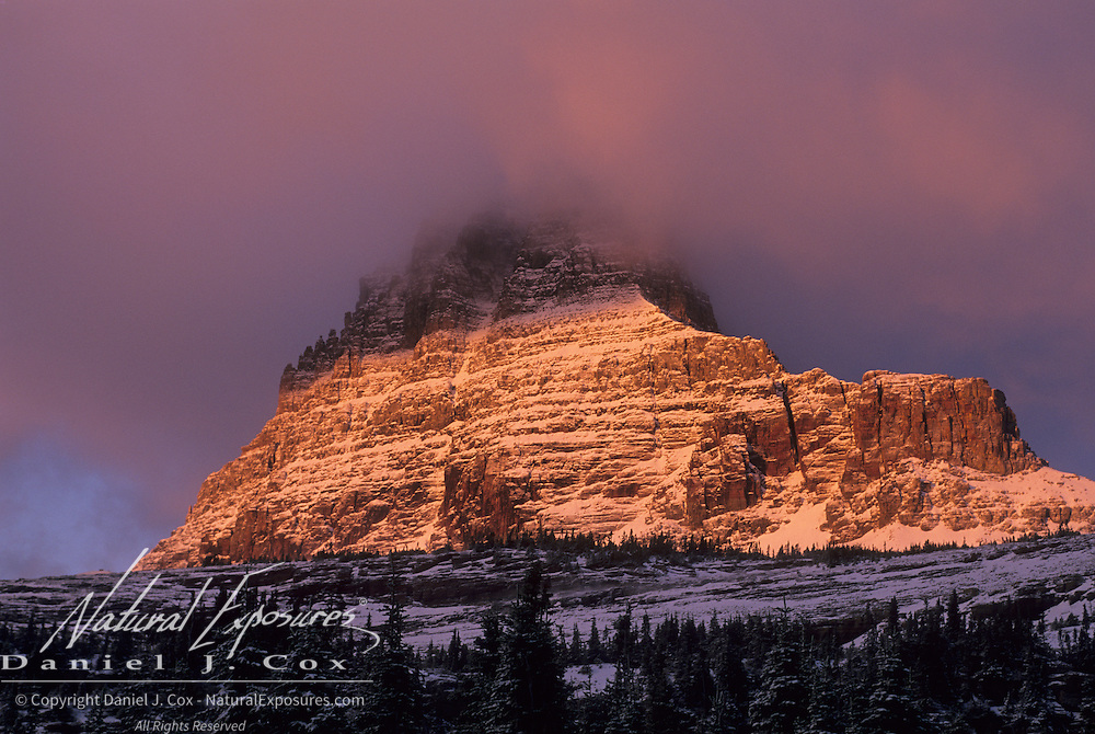 First snowfall in alpenglow on Mount Clements during the fall in Glacier National Park, Montana.