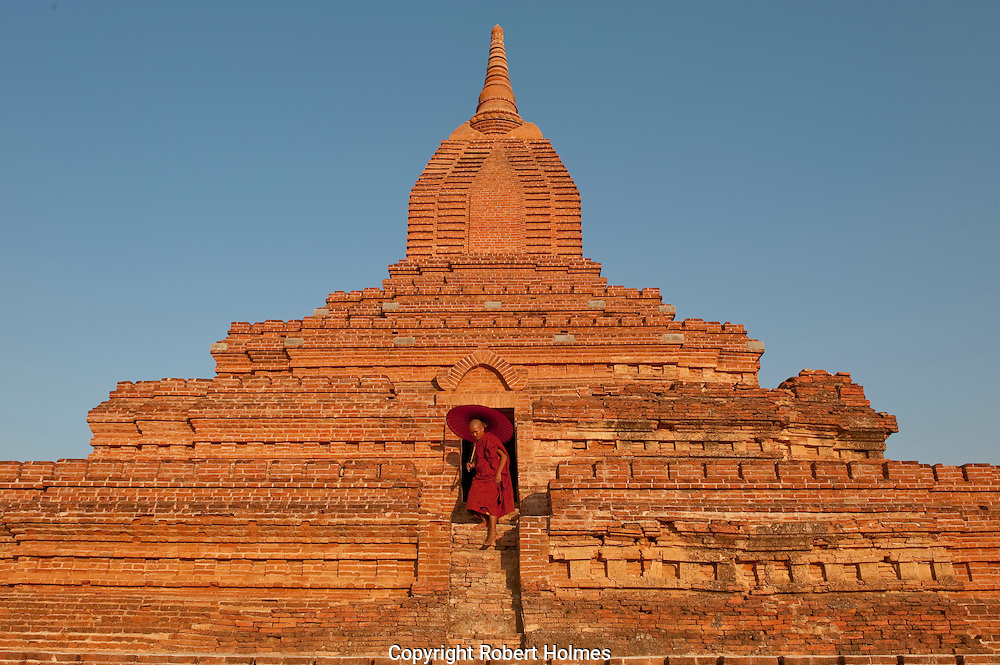 Monk with a parasol climbing one of Bagan's ancient pagodas