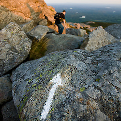 A hiker on the White Arrow Trail near the summit of Mount Monadnock in New Hampshire's Monadnock State Park.