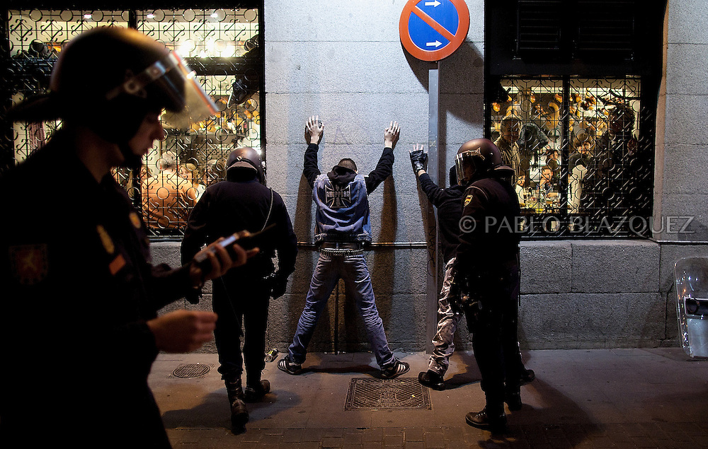 Policemen stop and check two youths during clashes following a demonstration organized by Spain's 'indignant' protesters at the Puerta del Sol square in Madrid on February 10, 2012, hours after Spain's right-leaning government unveiled a labour reform. The number of jobless people in Spain shot above five million at the end of 2011, sending the unemployment rate to 22.85 percent -- double the European average and the highest in the industrialized world. Placard reads 'Against the labour reform.'