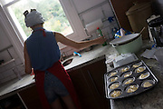 A 15 year-old teenager bakes party cakes in a domestic kitchen.