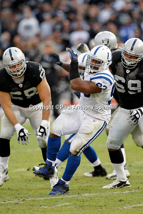 Indianapolis Colts defensive end Dwight Freeney (93) does his familiar spin move while breaking free of a double team block by Oakland Raiders offensive tackle Khalif Barnes (69) and Oakland Raiders offensive tackle Jared Veldheer (68) during the NFL week 16 football game against the Oakland Raiders on Sunday, December 26, 2010 in Oakland, California. The Colts won the game 31-26. (©Paul Anthony Spinelli)