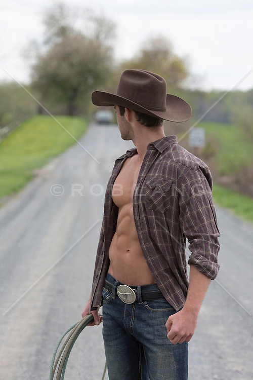 sexy cowboy with an open shirt on a road