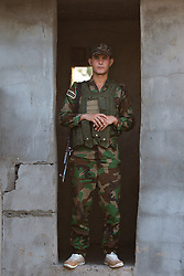 © Licensed to London News Pictures. 29/06/2014. Khanaqin, UK Khanaqin, Iraq. A Kurdish peshmerga fighter stands in the doorway of a sentry post at a Kurdish peshmerga base in Khanaqin, Iraq.<br /> <br /> The peshmerga, roughly translated as those who fight, is at present engaged in fighting ISIS all along the borders of the relatively safe semi-automatous province of Iraqi-Kurdistan. Though a well organised and experienced fighting force they are currently facing ISIS insurgents armed with superior armament taken from the Iraqi Army after they retreated on several fronts. Photo credit : Matt Cetti-Roberts/LNP