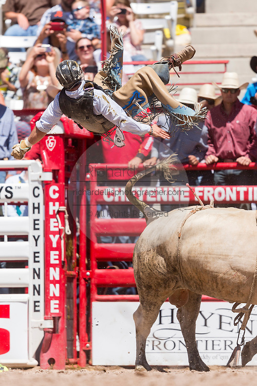 Bull rider Jeff Bertus is tossed from his bull during the Bull Riding finals at the Cheyenne Frontier Days rodeo in Frontier Park Arena July 26, 2015 in Cheyenne, Wyoming. Frontier Days celebrates the cowboy traditions of the west with a rodeo, parade and fair.