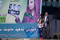 © Licensed to London News Pictures. 27/04/2014. Sulaimaniya, Iraq. Supporters of the Patriotic Union of Kurdistan (PUK) political party dance next to a PUK election poster during celebrations in the lead up to the 2014 Iraqi parliamentary elections in Sulaimaniya, Iraqi-Kurdistan.<br /> <br /> Although banned in other parts of Iraqi-Kurdistan, the days leading up to an election in Sulaimaniya sees political supporters of all the three main parties parading up and down the main street of the city, waving flags, honking horns, letting off fireworks and firing pistols and rifles into the air.<br /> <br /> The period leading up to the elections, the fourth held since the 2003 coalition forces invasion, has already seen six polling stations in central Iraq hit by suicide bombers causing at least 27 deaths. Photo credit: Matt Cetti-Roberts/LNP