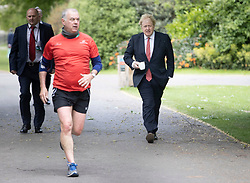 © Licensed to London News Pictures. 11/05/2020. London, UK. A jogger runs past as Prime Minister Boris Johnson walks in St James's Park in central London. The Prime Minister has announced a few changes to the lockdown rules. Photo credit: Peter Macdiarmid/LNP
