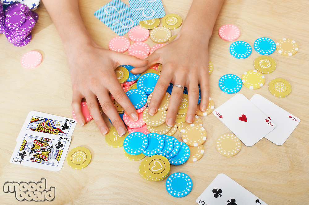 Hands of woman Grabbing Gambling Chips on table close up of hands overhead view
