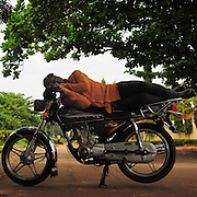 12-05-29   - LOME, TOGO -    Zemidjan ('take me quickly' in  Fon) driver Kodjo Apelete demonstrates how he sleeps on his motorcycle in Lomé, Togo on May 29. Underpaid, rarely thanked and working all hours to make a meagre living, they find very few moments of calm and quiet in their lives. And so, the moto-taxi men have perfected various ways of calmly sleeping on their motorbike as they wait for  their next customer. And so, on the move amidst the chaos and bustle of daily life, they relax and sleep.  Photo by Daniel Hayduk